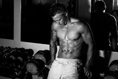 Bodybuilder after training in the gym. Bodybuilder after the training pass in front of line dumbbells Monochrome stock image