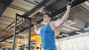 Bodybuilder training in the gym - young muscular man perform training for biceps, slider shot. Bodybuilder training in the gym - young muscular man perform Royalty Free Stock Images
