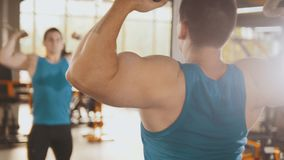 Bodybuilder training in the gym - young muscular man perform training for biceps near mirror. Slider Stock Images