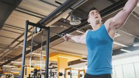 Bodybuilder training in the gym - young muscular man perform training for biceps, slider shot. Bodybuilder training in the gym - young muscular man perform Stock Images