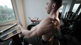 Bodybuilder during the training of hands. Bodybuilder during the training of hands on the simulator in the gym stock video footage