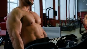 Bodybuilder training legs. Man doing exercise with weightlifting machine in fitness center. Muscle and fitness.  stock video