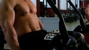 Bodybuilder training legs. Man doing exercise with weightlifting machine in fitness center. Muscle and fitness.  stock footage