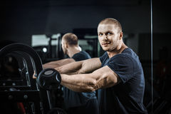 Bodybuilder in training. The bodybuilder after the training bodybuilder with pumped hand smiling in poses the weightlifter demonstrates his biceps powerlifting stock photo