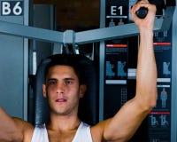 Bodybuilder training on shoulder machine. Bodybuilder man training on pec flye machine royalty free stock image