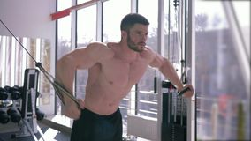 Bodybuilder training, strong athlete guy performs an exercise for muscle building workout on traction simulator while. Bodybuilder training, strong athlete guy stock video