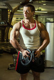 Bodybuilder trains the muscles in the gym. Fitness training Royalty Free Stock Images