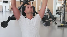 Bodybuilder trains on simulator for shoulder muscles in gym hall.  stock video