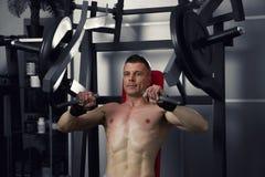 Bodybuilder trening na trenerze w gym, perfect mięśniowy męski ciało Obraz Stock