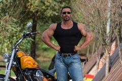 Bodybuilder und Motorrad lizenzfreies stockbild