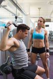 Bodybuilder using weight machine for arms with encouraging trainer Stock Photo