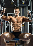Bodybuilder. Very brawny guy bodybuilder ,  execute exercise  on gym apparatus Butterfly Machine, in gym Royalty Free Stock Image