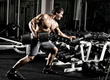 Bodybuilder. Very power athletic guy ,  execute  traction with  dumbbells, exercise on broadest muscle of back, in gym Royalty Free Stock Photos
