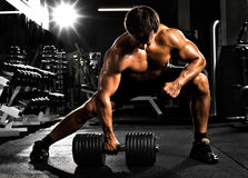 Bodybuilder. Very power athletic guy ,  execute  traction with  dumbbells, exercise on broadest muscle of back, in sport hall Royalty Free Stock Photography