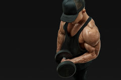 Bodybuilder wearing a red tank top. Close up shot of muscular bodybuilder wearing a red tank top and black cap doing biceps curl with dumbbell against black Stock Photos