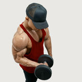Bodybuilder wearing a red tank top. Close up shot of muscular bodybuilder wearing a red tank top and black cap doing biceps curl with dumbbell against white Royalty Free Stock Image