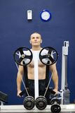 Bodybuilder with weight machine. Bare chested young bodybuilder using fixed weight machine in gym Stock Image