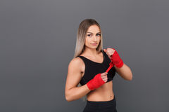 Bodybuilder woman banding her hands. Muscular young woman putting red tape on hands preparing to fight on the gray background Stock Photos