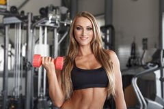 Bodybuilder woman with colorful dumbbells Stock Images