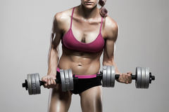 Bodybuilder woman with dumbbells.strong girl with muscles training in gym Royalty Free Stock Photo