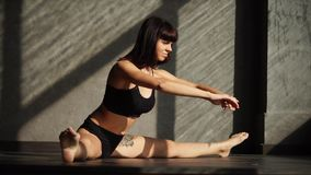 Bodybuilder woman is stretching legs muscles in a gymnastic hall. Sportswoman is extending legs, is in a split on a floor of a sunny gym. Static stretching stock footage
