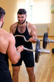 Bodybuilder working out biceps with barbell in front of mirror. Stock Photography