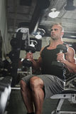 Bodybuilder working out with bumbbells weights at Stock Photos