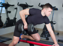 Bodybuilder working out with bumbbells weights at the gym Stock Photo
