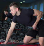 Bodybuilder working out with bumbbells weights at the gym.  Stock Images