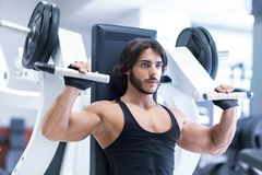 Bodybuilder working out with shoulder press machine. Fit adult bodybuilder working out with shoulder press machine in a gym during training in a healthy active royalty free stock photo