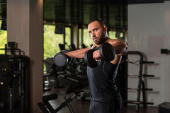 Bodybuilder Working Out Shoulders In The Gym. Big Man Standing Strong In The Gym And Exercising Shoulders With Dumbbells - Muscular Athletic Bodybuilder Model Royalty Free Stock Photo