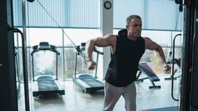 Bodybuilder workout in gym machine stock video
