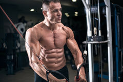 Bodybuilder works out pushing up excercise in gym Stock Photography