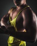 Bodybuilder. Young bodybuilder exercising with dumbbells on dark background Stock Image