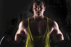 Bodybuilder. Young bodybuilder exercising with dumbbells on dark background Stock Photography