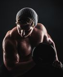 Bodybuilder. Young bodybuilder exercising with dumbbells on dark background Stock Photo