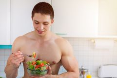 Bodybuilder young man eating salad in the kitchen copyspace heal. Thy eat vegan smiling Royalty Free Stock Photo