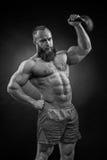Bodybuilder z brodą podnosi ciężkiego kettlebell zdjęcie royalty free
