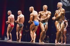 Bodybuilder zeigen ihre beste Kastenhaltung in einem Aufstellungsvergleich Stockfotografie