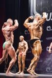 Bodybuilder zeigen ihre hinteren doppelten Bizepse auf Stadium in den Meistern Lizenzfreie Stockfotografie
