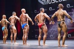 Bodybuilder zeigen ihre Konstitution auf Stadium in der Meisterschaft Stockbilder