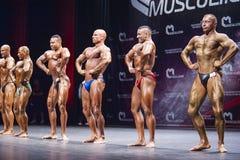 Bodybuilder zeigen ihre Konstitution auf Stadium in der Meisterschaft Lizenzfreie Stockfotos