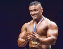 Bodybuilder zeigt seine Medaillen auf Stadium Stockfotografie