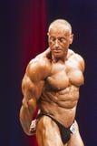 Bodybuilder zeigt Trizepshaltung auf Stadium in der Meisterschaft Lizenzfreies Stockfoto