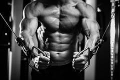 Bodybuilderkerl in den Turnhallenhänden schließen oben