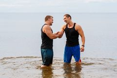 Bodybuilders on the beach Stock Images