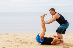 Bodybuilders on the beach Stock Photos