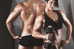 Bodybuilders. Fitness couple. Bodybuilders. Fitness couple - women and men with dumbbells in gym. Toning stock photos