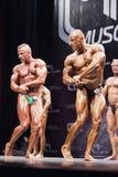 Bodybuilders pokazują ich klatki piersiowej pozę na scenie w mistrzostwie Zdjęcia Royalty Free