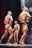 Bodybuilders pokazują ich lats rozprzestrzeniającą pozę na scenie w championshi Obrazy Royalty Free